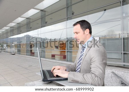 Man in business travel working on laptop computer - stock photo