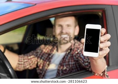 Man in car driving showing smart phone display smiling happy. Focus on smartphone. - stock photo