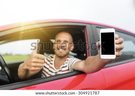 Man in car showing smart phone display and showing thumb up. Focus on mobile phone. - stock photo
