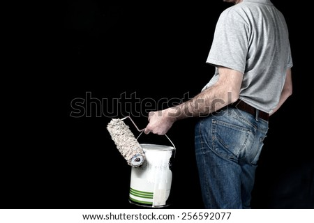 Man in casual clothes holding paint roller and a bucket of paint - stock photo