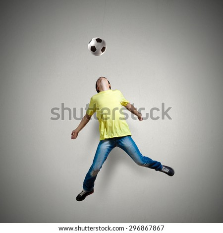 Man in casual kick football ball over head - stock photo
