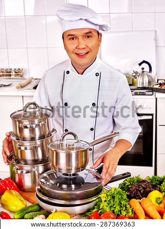 Man in chef hat cooking at professional kitchen. - stock photo