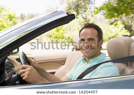 Man in convertible car smiling - stock photo
