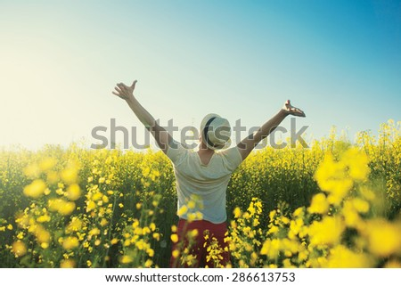 Man in country in summer day in yellow flowers - stock photo