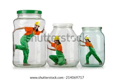 Man in coveralls imprisoned in glass jar - stock photo