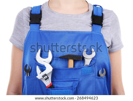 Man in coveralls with tools in his pocket, closeup - stock photo