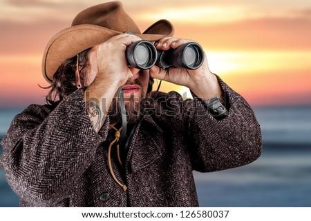 Man in cowboy hat looking through binoculars - stock photo