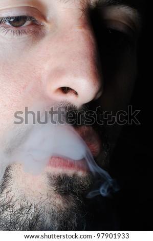 Man in dark exhaling cigarette smoke - stock photo