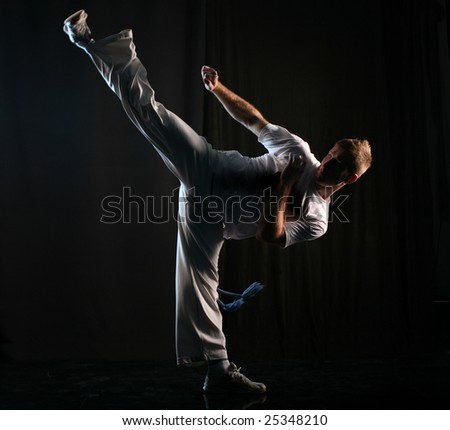 Man in dark practice martial art - high kick - stock photo