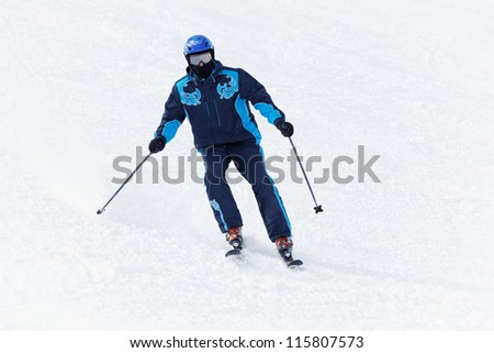 Man in darkblue ski suit glides downhill on skis - stock photo