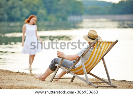 Man in deck chair on a beach of a lake looking to woman in water - stock photo