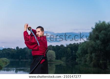 Man in ethnic samurai japanese clothing uniform with katana sword - stock photo