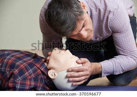 Man In First Aid Class Checking Airway On CPR Dummy - stock photo