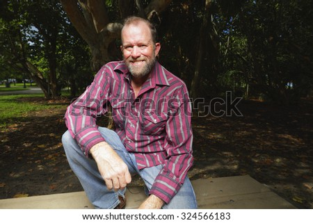 Man in flannel posing in a park - stock photo