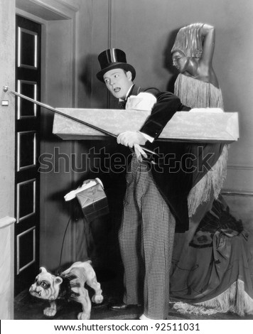 Man in formal clothing and a dog trying to ring the bell with his walking stick - stock photo