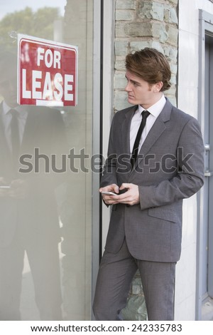 """man in front of a store with a """"for lease"""" sign - stock photo"""