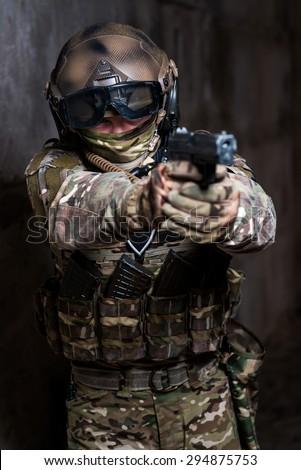 Man in full military ammunition holding a gun - stock photo