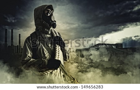 Man in gas mask against disaster background. Pollution concept - stock photo