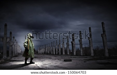 Man in gas mask and camouflage holding gun. Disaster concept - stock photo