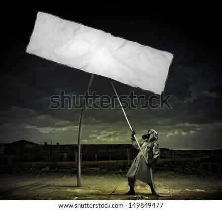 Man in gas mask and camouflage pulling blank banner. Place for text - stock photo