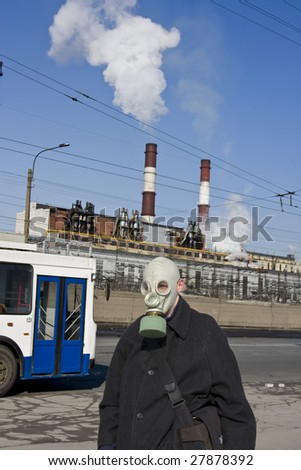 Man in gas mask on background of city of landscape with pipes and smoke - stock photo
