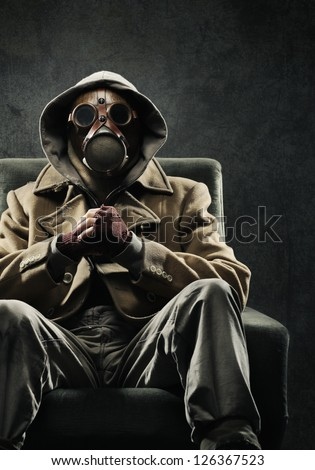 Man in gas mask sitting in a chair - stock photo