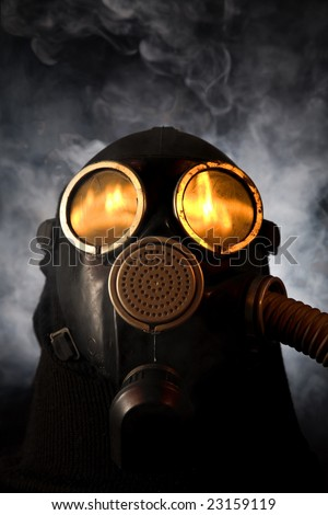 Man in gas mask with fire reflection in the eyes over smoky background - stock photo