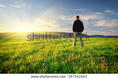 Man in green meadow. Conceptual scene. - stock photo