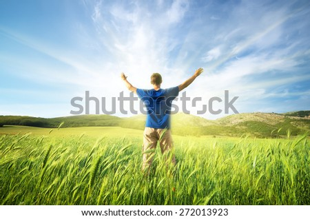 Man in green meadow of wheat. Emotional scene. - stock photo