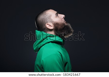 Man in green sweatshirt, looking up  - stock photo