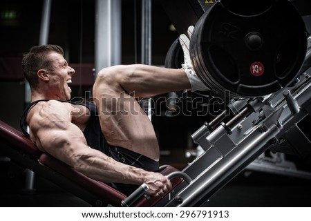 Man in gym training at leg press to define his upper leg muscles - stock photo