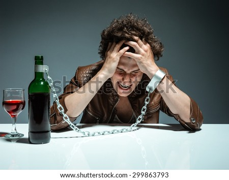 Man in handcuffs interconnected with a bottle of alcohol / photo of youth addicted to alcohol, alcoholism concept, social problem - stock photo