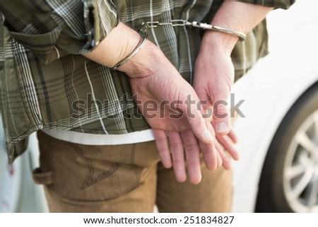 Man in handcuffs standing by his car close up - stock photo