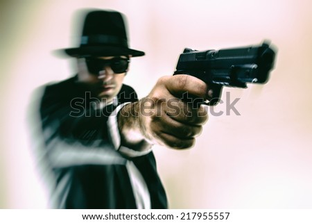 Man in Hat Pointing Gun. Man in suit, hat and sunglasses pointing a gun with action blur. - stock photo