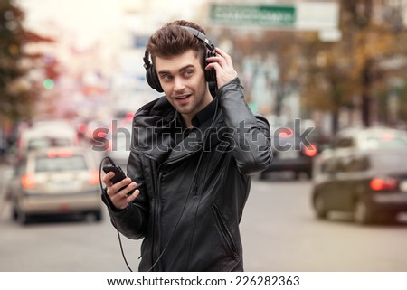 man in headphones on the street. Standing with phone in hand - stock photo