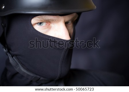 Man in helmet and mask staring at you over dark background - stock photo