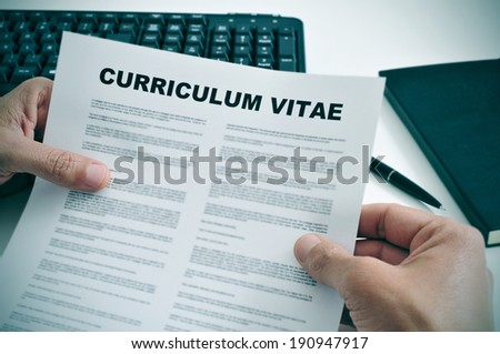 man in his office checking a curriculum vitae - stock photo