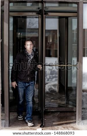 Man in his twenties walks through a revolving doorway entrance. - stock photo