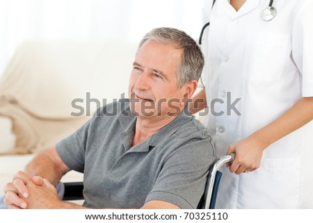 Man in his wheelchair with his nurse at home - stock photo