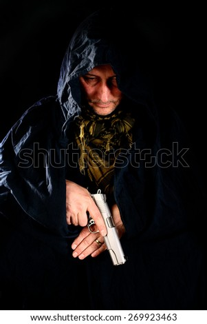 man in hood holding a pistol over black - stock photo