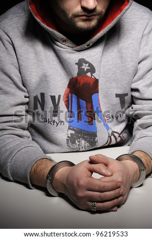 Man in hooded jacket sitting at table in handcuffs. The face in the shadows - stock photo