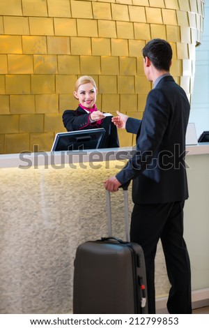 Man in Hotel check in at reception or front office being given key card - stock photo