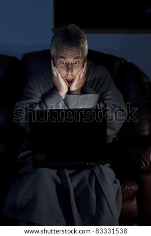 Man in housecoat working late series surprised - stock photo