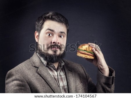 Man in jacket with beard holding hamburger at dark background - stock photo