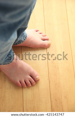 Man in jeans with bare feet on floor with copy space - stock photo