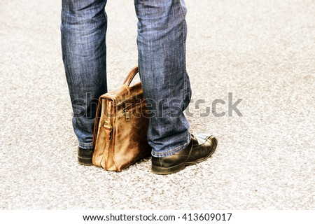 Man in jeans with leather suitcase waiting - stock photo