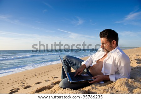 man in jeans working in a laptop at the beach - stock photo