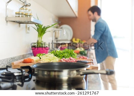 Man in kitchen cooking lunch - Focus on food - stock photo