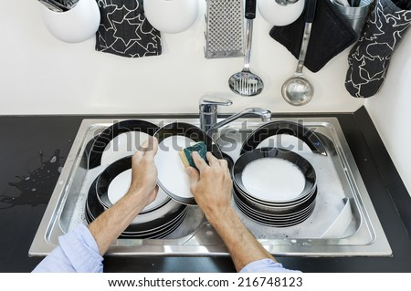 Man in kitchen who cleans the dishes - stock photo