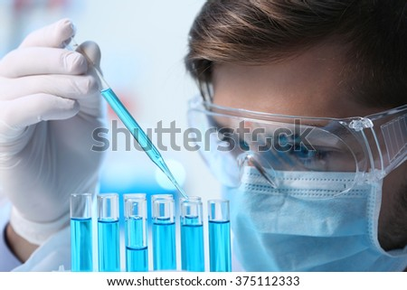 Man in laboratory checking test tubes - stock photo